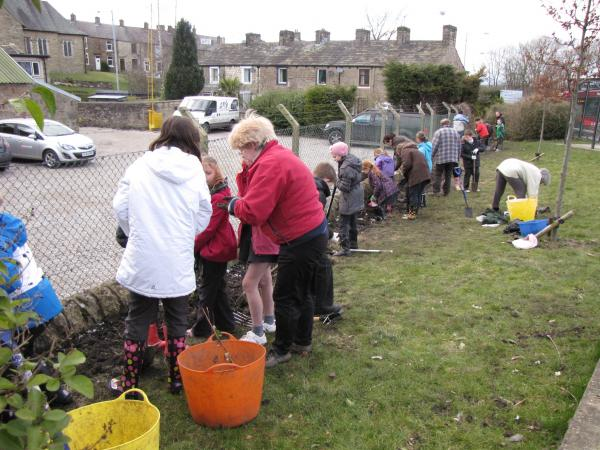 Local children and Barnoldswick in Bloom volunteers platning a hedge last year