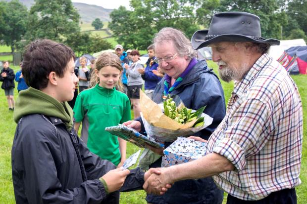 Ben Bradley, representing Settle Scouts, and Rachel Weller from Ingleton, present gifts to Mary Anne and Dave Burrows at the recent Survival Camp at Austwick