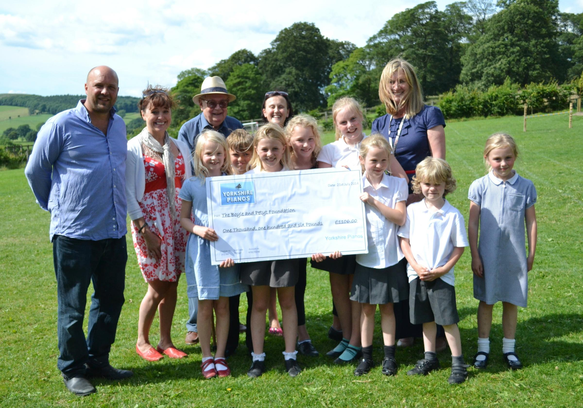 Parents and children from Beamsley's Boyle and Petyt School receive a cheque from Adam Cox of Yorkshire Pianos (on the far left), foundation governor Colin Crabtree and headteacher Imogen Addy