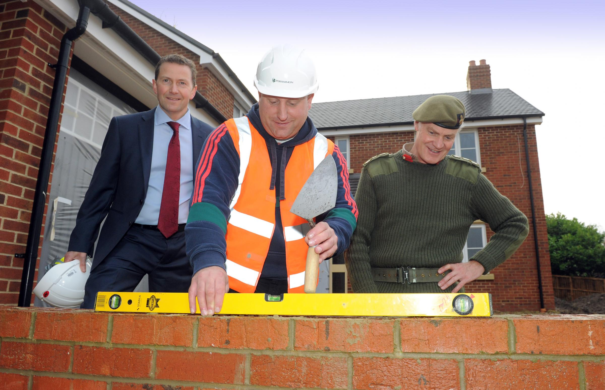 Jeff Fairburn, group CEO, Persimmon plc with ex-forces serviceman Ross Wilson who is training to be a bricklayer with Brigadier Greville Bibby looking on. (13512047)