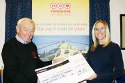 Amanda Kilner hands over her cheque to Yorkshire Air Ambulance's Tony Doveston.