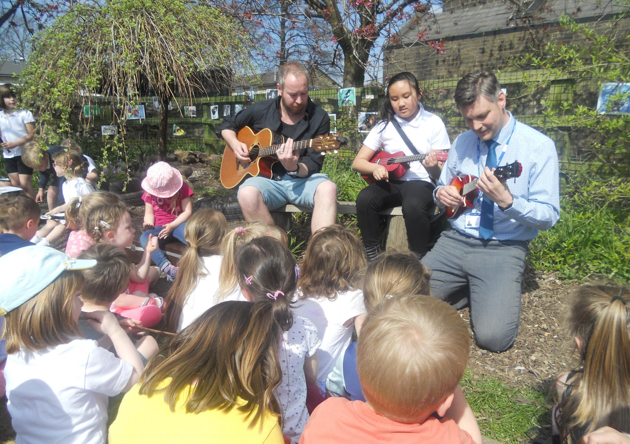 Parent Mr Keeton plays the guitar while pupil Carly Chan and headteacher Richard Hunt demonstrate their ukulele skills