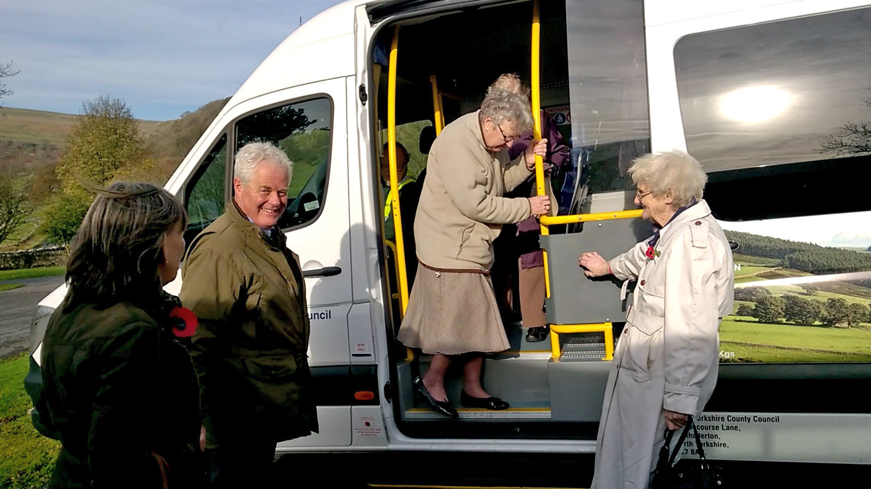 Craven District Councillor Chris Clark and volunteer driver Gill Owen watch as Muriel Raw and Mary Hurst from Kettlewell and Megan Lightfoot from Buckden try out the bus