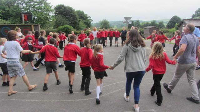Pupils and staff dance the hokey-cokey in memory of former dinner lady Christine Hawkins