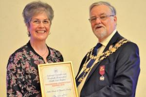 Settle Amateur Operatic Society chairman Trudi Wilson receives an award from John W Barnes, chairman of the National Operatic and Dramatic Association.