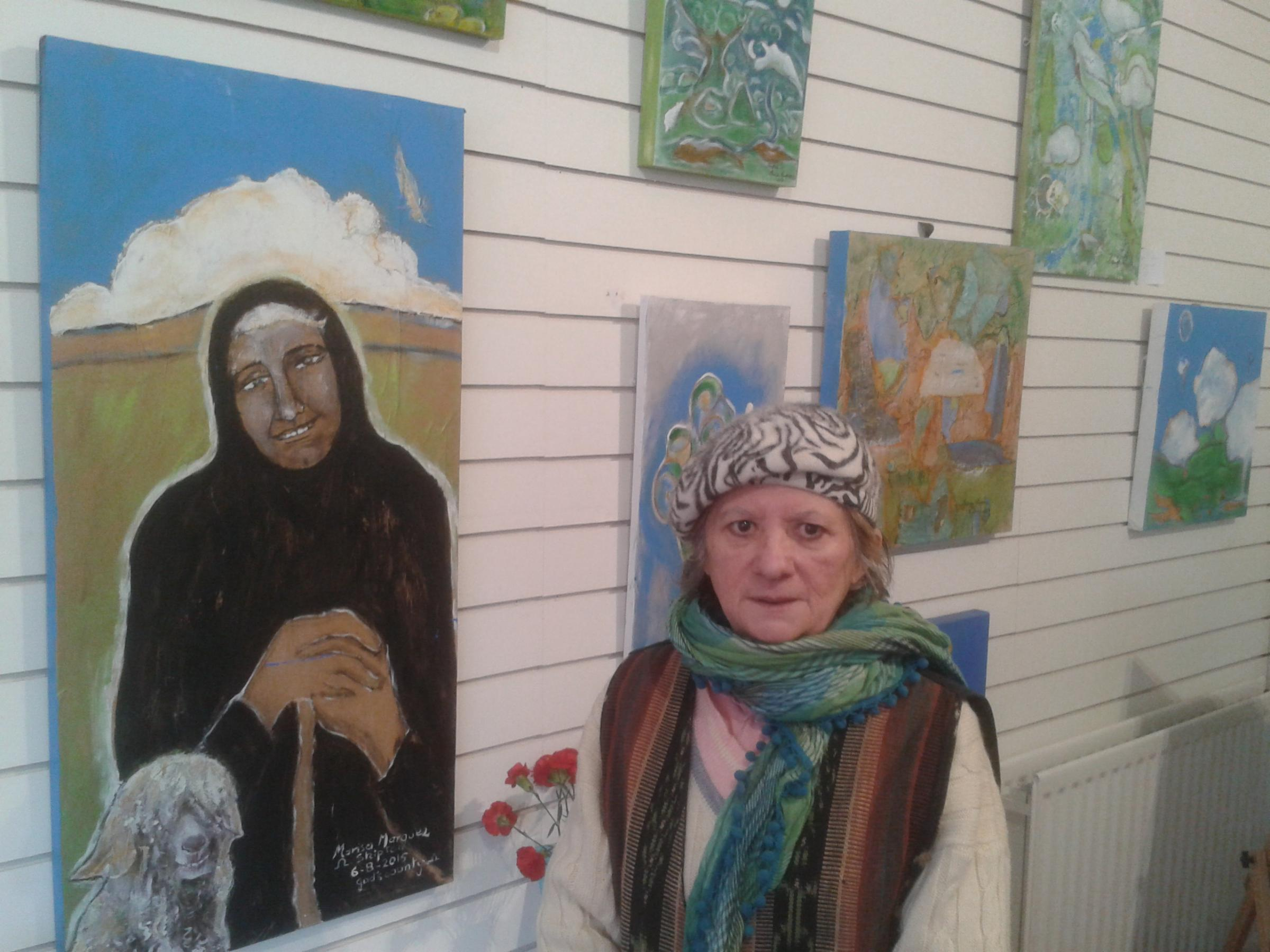 Artist Marisa Marquez with some of her paintings in the Sheepton exhibition.