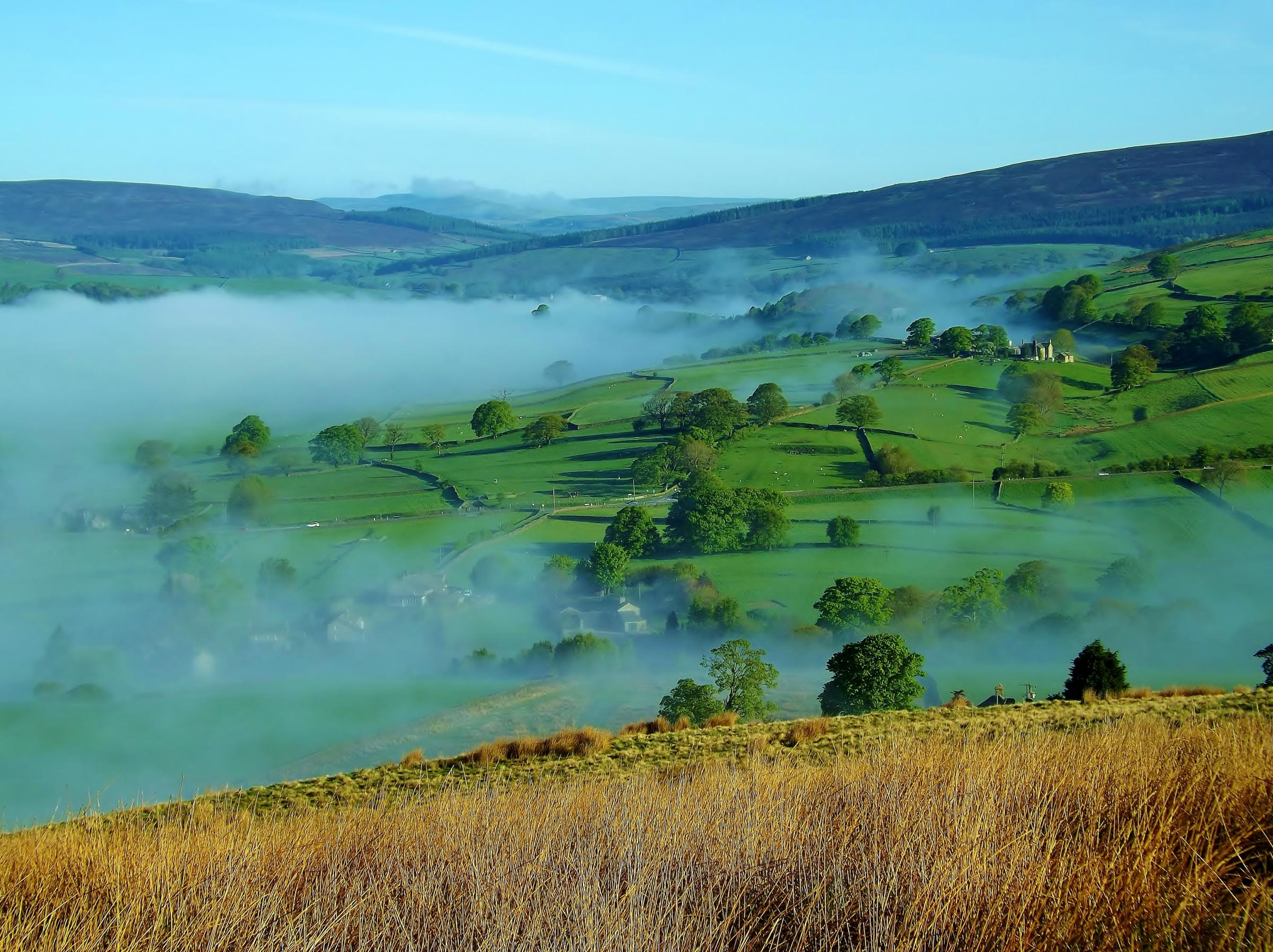 The view looking up Wharfedale from Beamsley Beacon, as the valley mist clears early on a bright spring morning. By Roger Nelson of Bolton Abbey