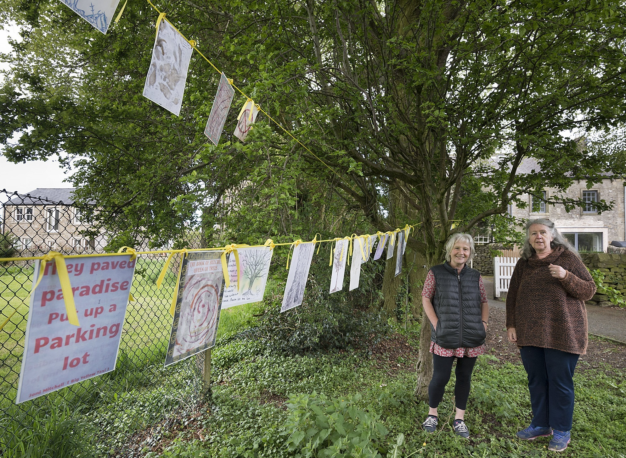 ROOTS campaigner Jenny Hall, left, with artist Susan Askew  at the installation around the 150-year-old beech tree in Settle which is under threat from pitch drainage improvements