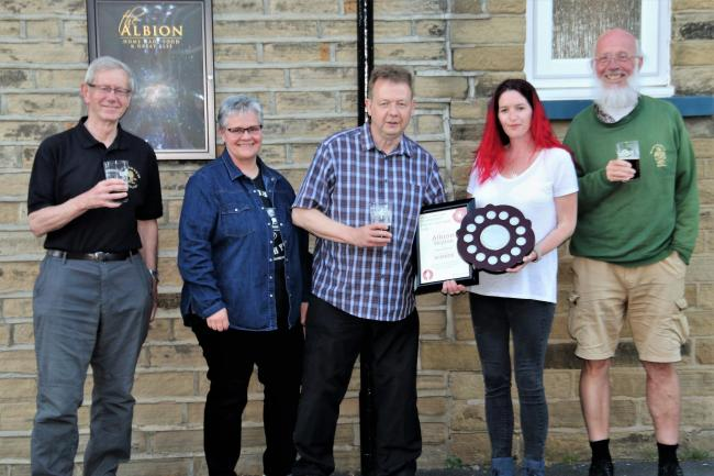 Albion Inn licensees Sera and Andrew Brook accept the 'community pub' award from CAMRA members