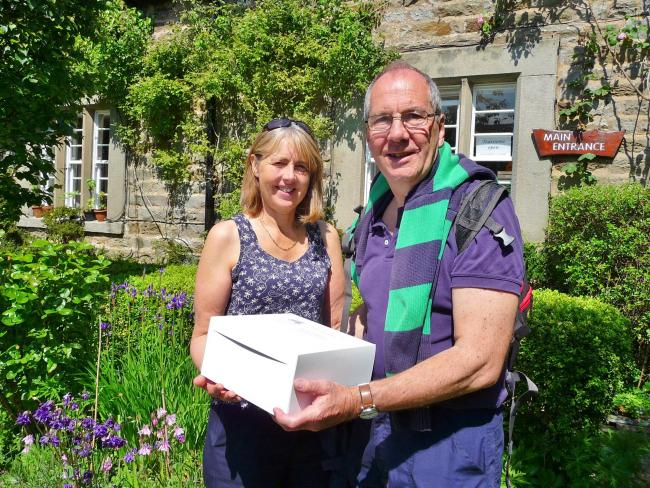 Carol and Tony Walker in the garden at West Winds, with their box of cakes