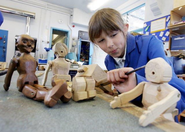Alexandra Whitaker works on her traditional wooden jig doll